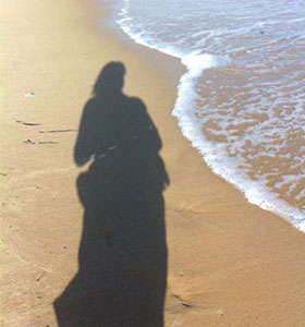 person's shadow on beach