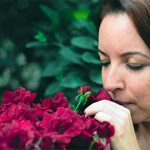 woman smelling red rose