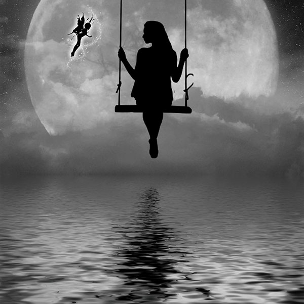 silhouetted woman on a swing in front of moon