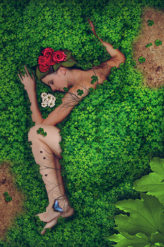 naked woman lying amid leaves and flowers