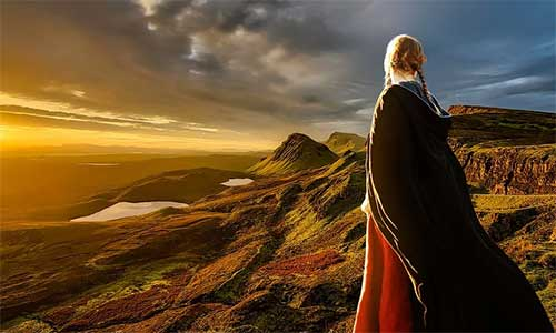 woman in a cape looking out over hills